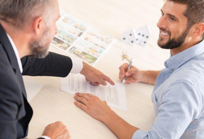 Responsabilidade Civil do Síndico - Homem de camisa azul assinando um papel e o outro homem de camisa branca e terno preto esta apontando onde ele deve assinar.